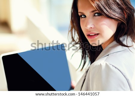 Young smiling woman sitting with laptop computer - stock photo