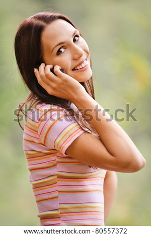 Young smiling woman speaks by mobile phone. - stock photo