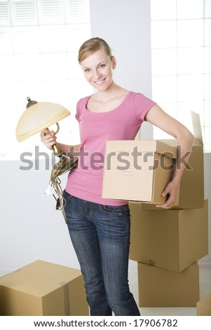 Young smiling woman standing between cardboard boxes. She's holding lamp and box in hands. She's looking at camera. - stock photo