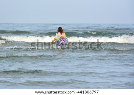 Young smiling woman standing in sea waves - stock photo
