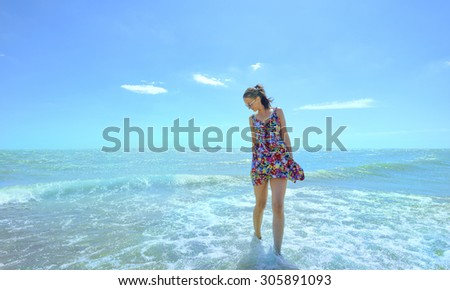 Young smiling woman standing in sea waves and holding her dress - stock photo