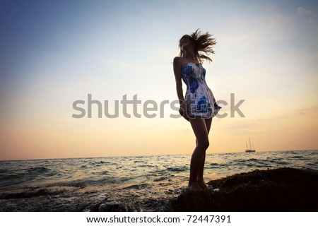 Young smiling woman standing on rock near sea and holding her dress - stock photo