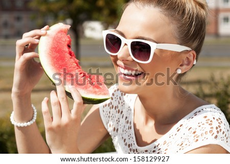 Young smiling woman takes watermelon from the opened fridge full of vegetables and fruit. Concept of healthy and dieting food - stock photo