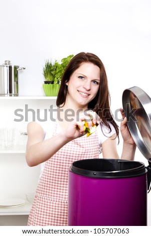 young smiling woman throwing away some organic waste - stock photo