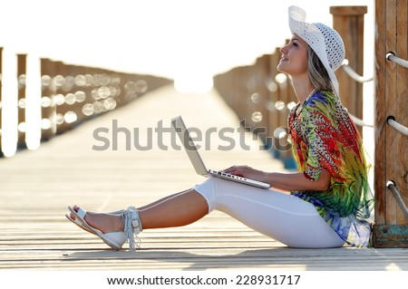 young smiling woman using laptop outdoor in summer - stock photo