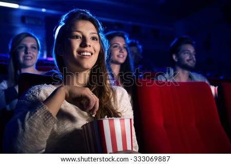 Young smiling woman watching a film in the movie theater and eating popcorn, entertainment and cinema concept - stock photo