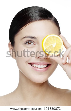 young smiling woman with a lemon slice in front of her eyes - stock photo