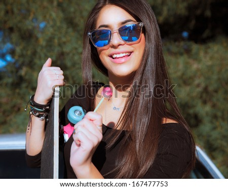 Young smiling woman with a lollipop. Cute female . Smiling style . Portrait with a sunglasses .Outdoors shot. Horizontal - stock photo