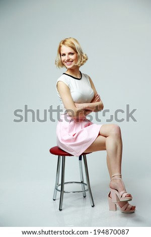 Young smiling woman with arms folded sitting on gray background - stock photo