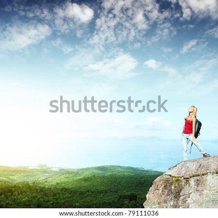 Young smiling woman with backpack standing on cliff's edge and looking to a sky - stock photo