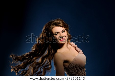 young smiling woman with flying long thick curly hair on dark studio background - stock photo