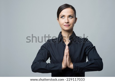 Young smiling woman with hands clasped looking away, yoga position. - stock photo