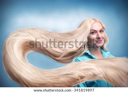 Young smiling woman with long blond hair - stock photo