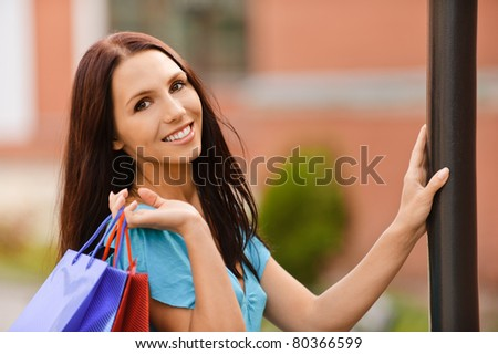Young smiling woman with multi-colored packages is glad to purchases. - stock photo