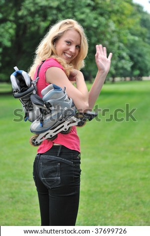 Young smiling woman with roller skates giving good bye gesture with hand. Outdoors in park. - stock photo