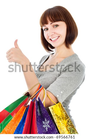 Young smiling woman with shopping bags make her thumb up, isolated on white - stock photo