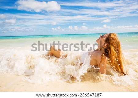 young smiling woman with sunglasses laying on beach covered in ocean waves on tropical blue sea sky background. Paradise getaway nature destination travel vacation concept. Positive face expression - stock photo