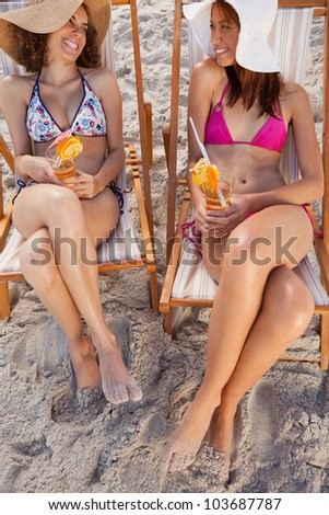 Young smiling women holding exotic cocktails while looking at each other - stock photo