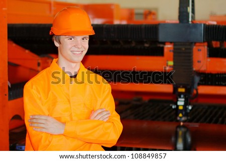 Young smiling worker with a working laser on a background - stock photo
