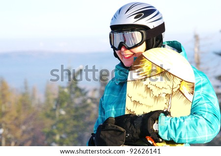 young snowboarder girl in winter clothes with snowboard - stock photo