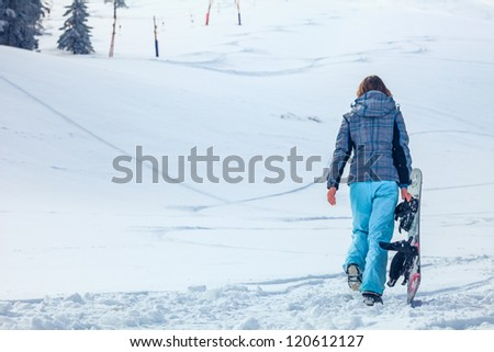 young snowboarder girl in winter clothes with snowboard in her hands - stock photo