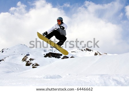 Young Snowboarder Jumping high over the snow - stock photo