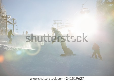 Young snowboarder man on the slope.Male snowboarder on the slopes on a sunny morning in the Alps.Expert male snowboarder.Snowboarder at a ski resort in the mountains.Winter vacation.Sun flare.Backlit - stock photo