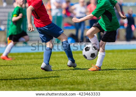 Young soccer football players playing match at sports field. Football soccer match for children. Kids playing soccer game tournament cup. Physical education classes at school. - stock photo