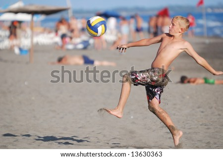 young soccer player at beach kicking ball - stock photo