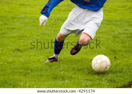 young soccer player kicking during a game - stock photo