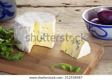 young soft blue cheese from France with wedge cut, some crockery, plums and some herbs on a rustic wooden table - stock photo
