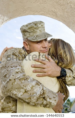 Young soldier embracing his woman outdoors - stock photo