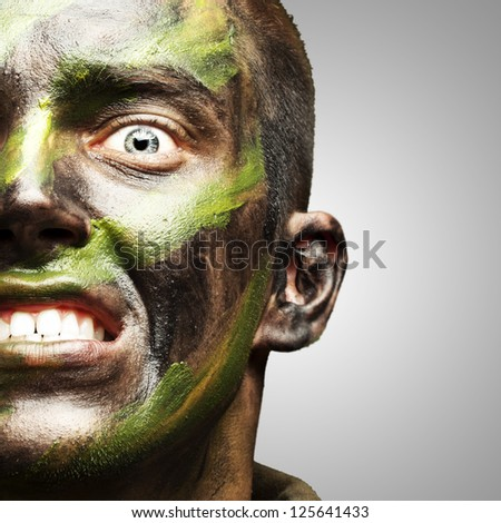young soldier face with camouflage paint over grey - stock photo
