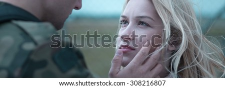 Young soldier is leaving his girlfriend - stock photo