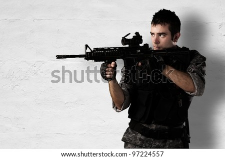young soldier pointing with a rifle against a white wall - stock photo