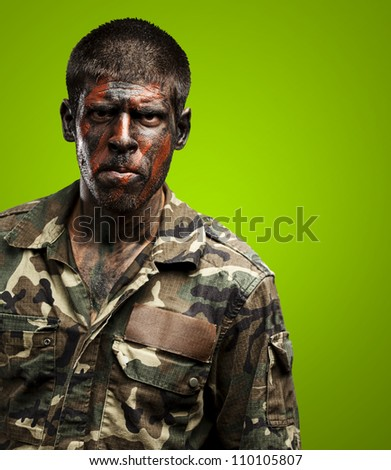 young soldier with camouflage paint looking very serious over green - stock photo