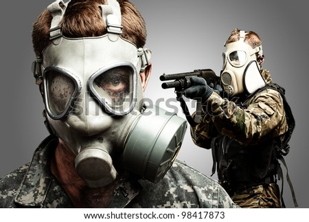 young soldiers wearing gas mask over grey background - stock photo