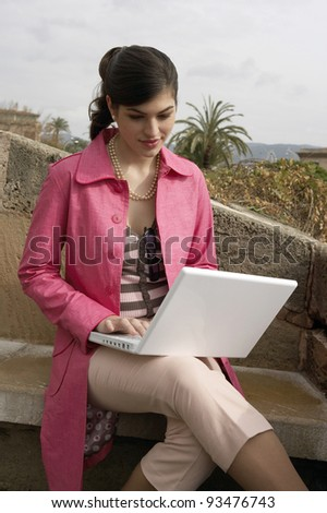 Young sophisticated woman using a laptop outdoors. - stock photo