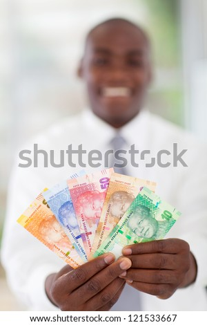 young south african businessman holding new bank notes - stock photo