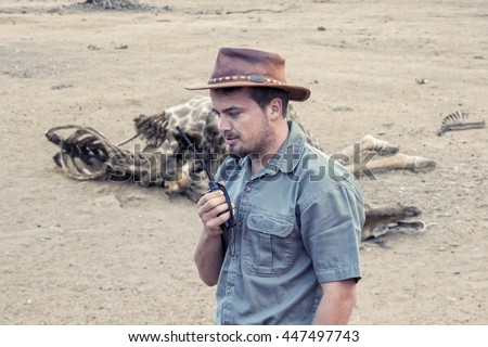 Young south african wildlife ranger with walkie talkie sends information about found dead body of a giraffe to the headquarter. - stock photo