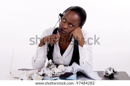 Young South African woman overwhelmed by work, telephones and boredom - stock photo
