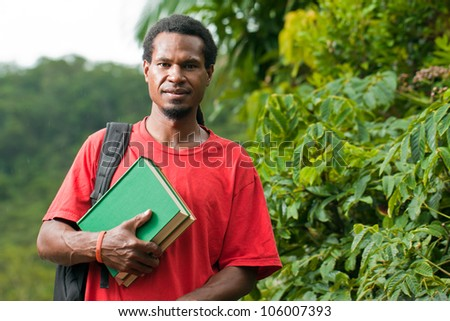 Young south east asian male student carrying books and backpack - stock photo