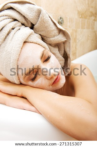 Young spa woman relaxing in bathroom with cream moisturizer.  - stock photo