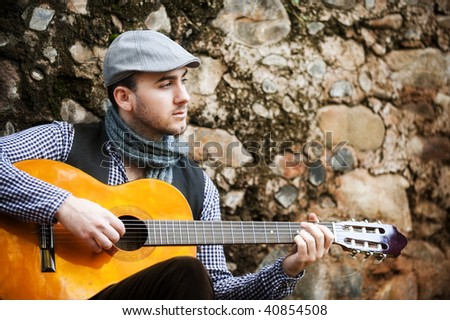Young spanish man playing classic guitar - stock photo