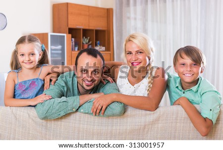 young spanish parents with two children posing in home interior - stock photo
