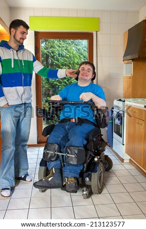 Young spastic male infantile cerebral palsy patient caused by birth complications sitting in a multifunctional wheelchair listening to music on headphones aided by a carer smiling with pleasure - stock photo