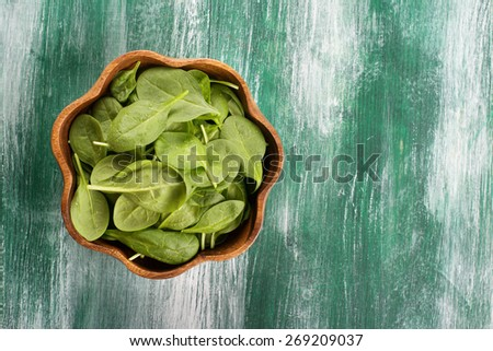Young spinach leaves in a wooden bowl on wooden green background. Top view - stock photo