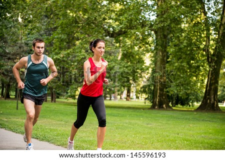 Young sport couple in starting position prepared to compete and run - stock photo