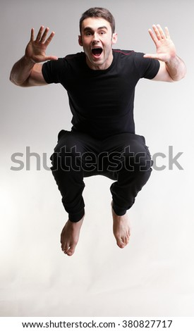 Young sport man jumping over grey background - stock photo