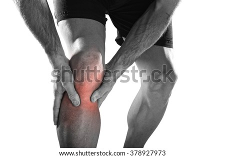 young sport man with strong athletic legs holding knee with his hands in pain after suffering ligament injury during a running workout training isolated on white background in black and white - stock photo